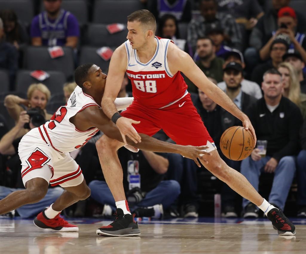 Chicago Bulls guard Kris Dunn, left, reaches for the ball against Sacramento Kings forward Nemanja Bjelica during the first quarter of an NBA basketba...