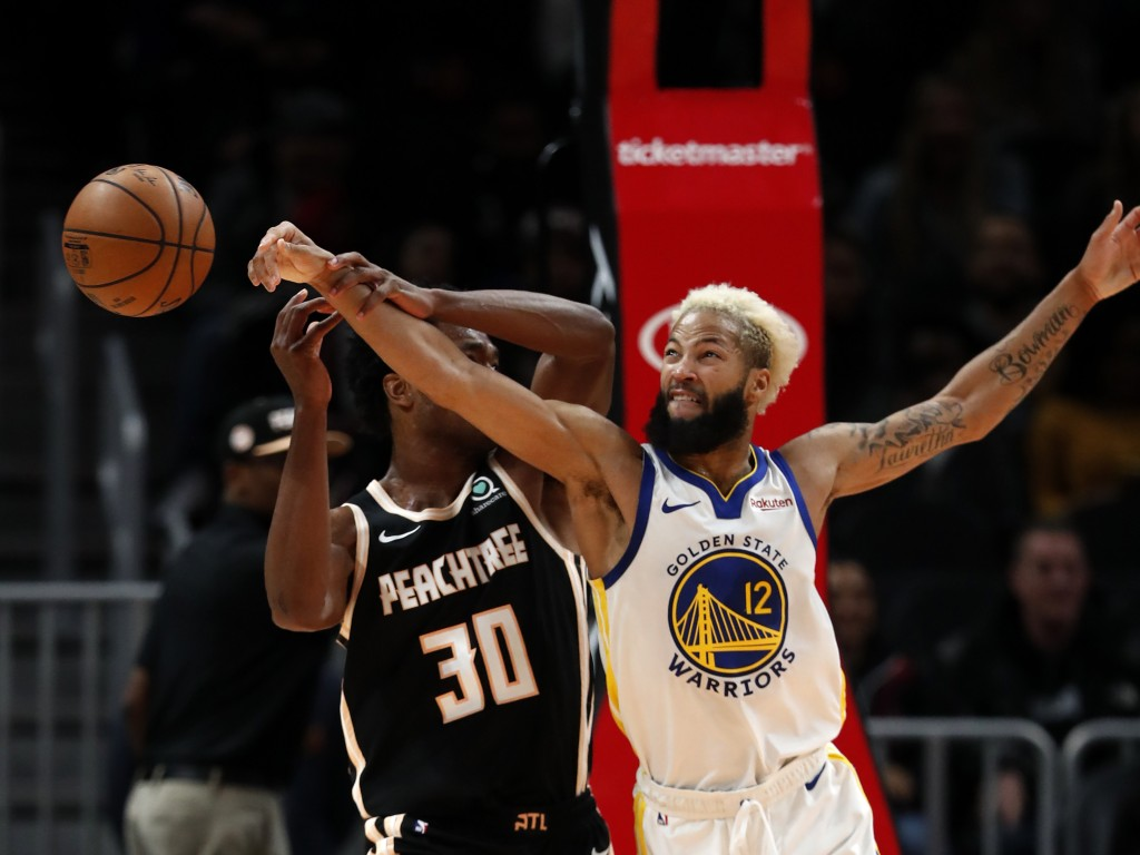 Golden State Warriors guard Ky Bowman (12) steals the ball from Atlanta Hawks center Damian Jones (30) in the second half of an NBA basketball game Mo...