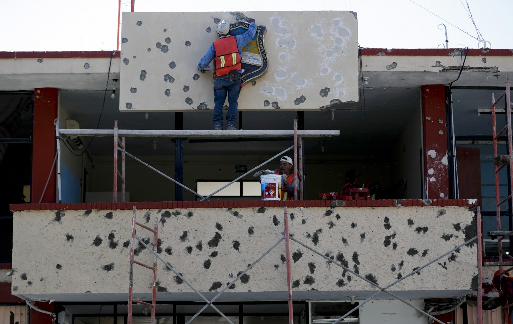 Workers repair the facade of City Hall riddled with bullet holes, in Villa Union, Mexico, Monday, Dec. 2, 2019. The small town near the U.S.-Mexico bo...
