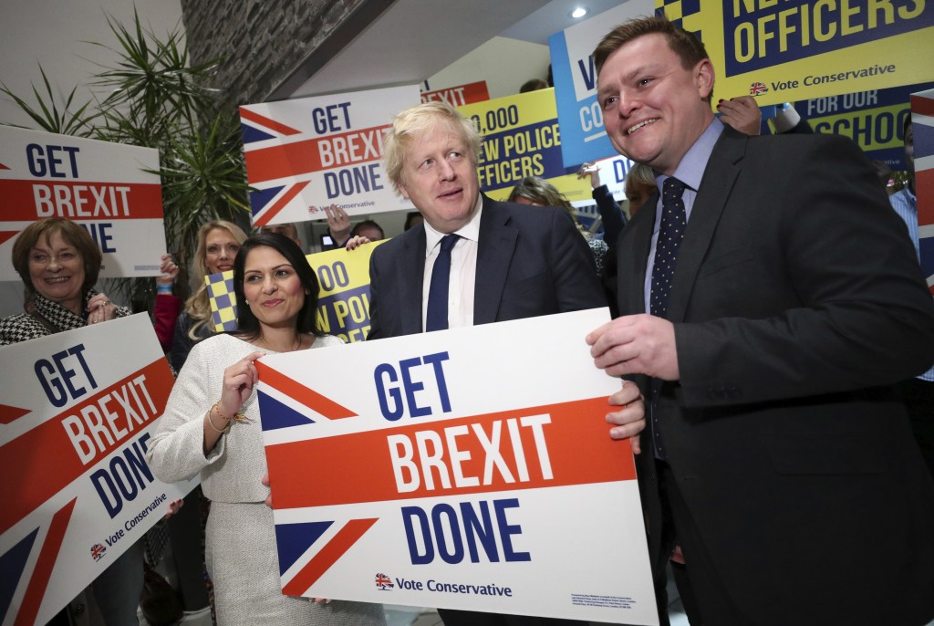 Home Secretary Priti Patel, center left, Britain's Prime Minister Boris Johnson, center, and MP Will Quince pose holding a sign before a rally event a...
