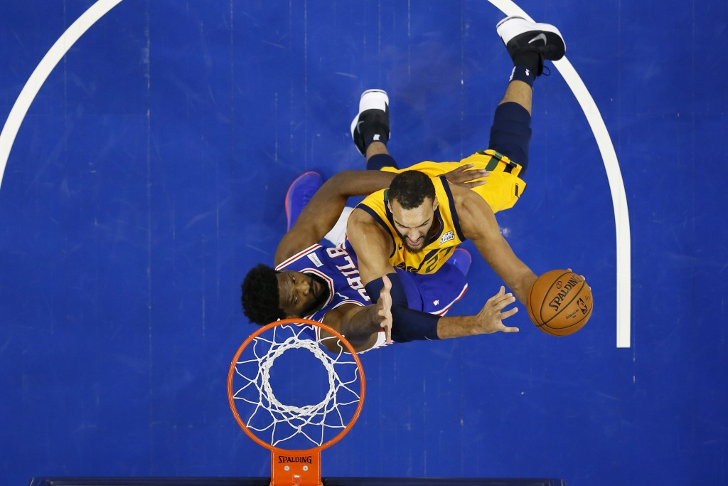 Utah Jazz's Rudy Gobert, right, goes up to shoot against Philadelphia 76ers' Joel Embiid during the first half of an NBA basketball game, Monday, Dec....