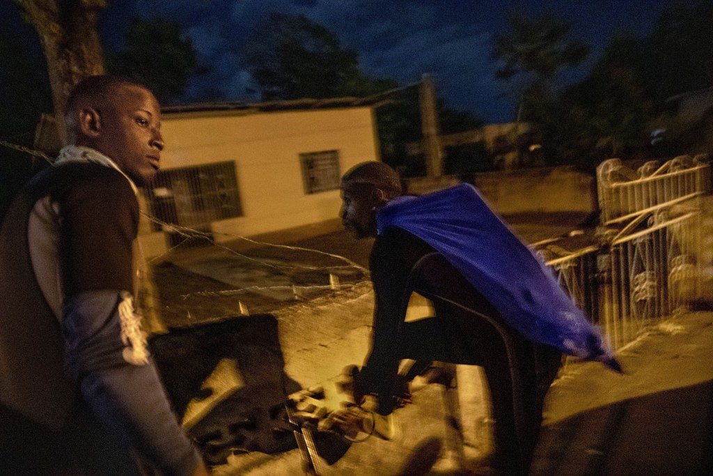 Nicholas Bingham, left, and Delroy Gooden, prepare to climb over a wall to go night spearfishing, which is banned, in Stewart Town, Jamaica, Friday, F...
