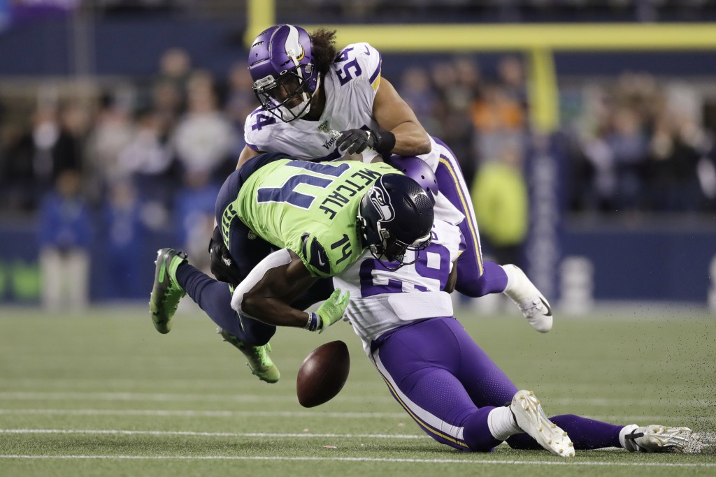 Seattle Seahawks' DK Metcalf (14) fumbles while being hit by Minnesota Vikings' Xavier Rhodes (29) and Eric Kendricks (54) during the second half of a...