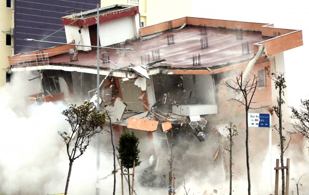The Albanian army uses a remote-controlled explosion to demolish a building in the western port city of Durres, Albania, Tuesday, Dec. 3, 2019. A remo...