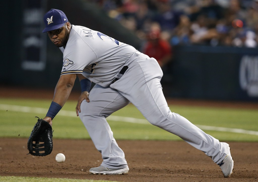 FILE - In this Sunday, July 21, 2019, file photo, Milwaukee Brewers first baseman Jesús Aguilar goes after a grounder during the sixth inning of a bas...