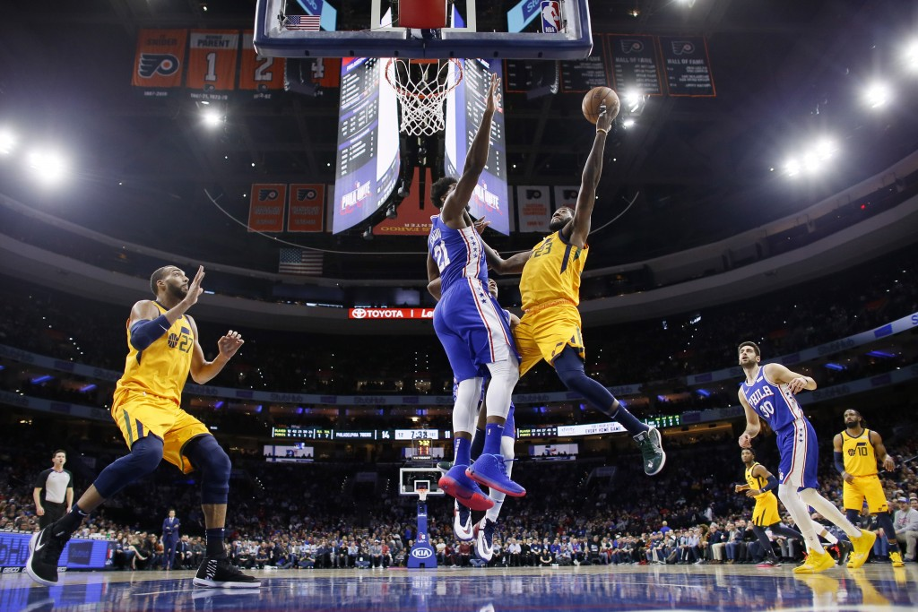 Utah Jazz's Royce O'Neale (23) goes up to shoot against Philadelphia 76ers' Joel Embiid (21) during the first half of an NBA basketball game, Monday, ...