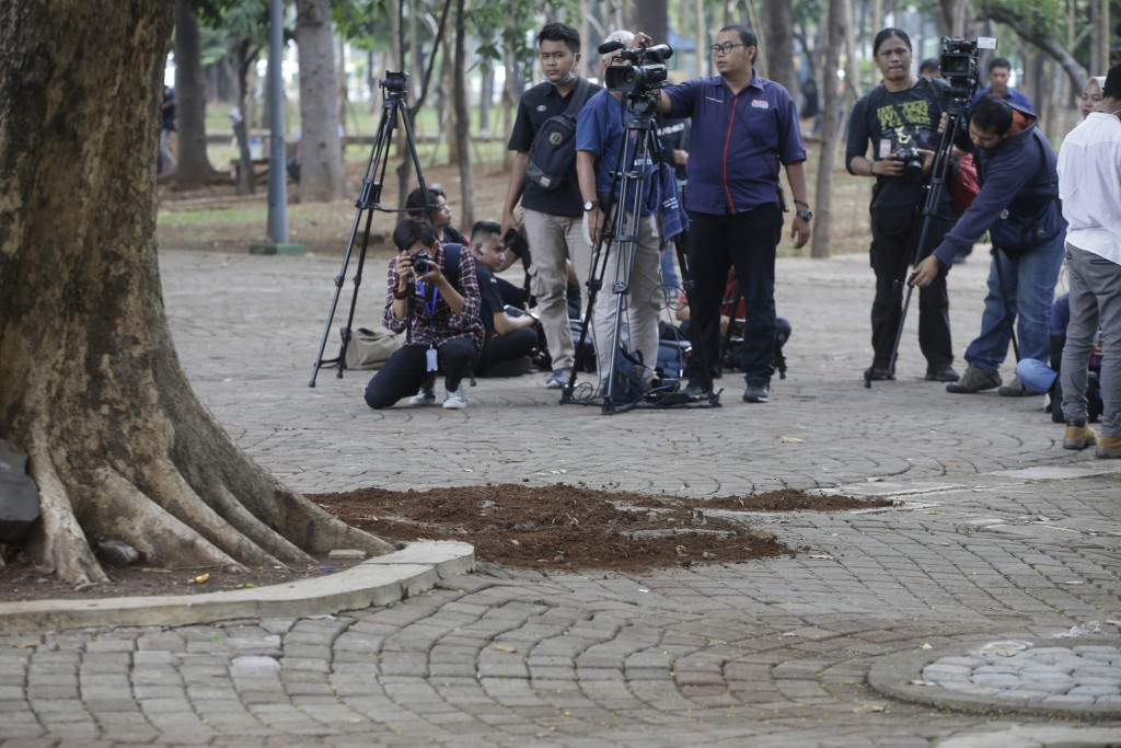 Journalists take pictures of the site of an explosion in Jakarta, Indonesia, Tuesday, Dec. 3, 2019. An explosion from a smoke grenade occurred Tuesday...