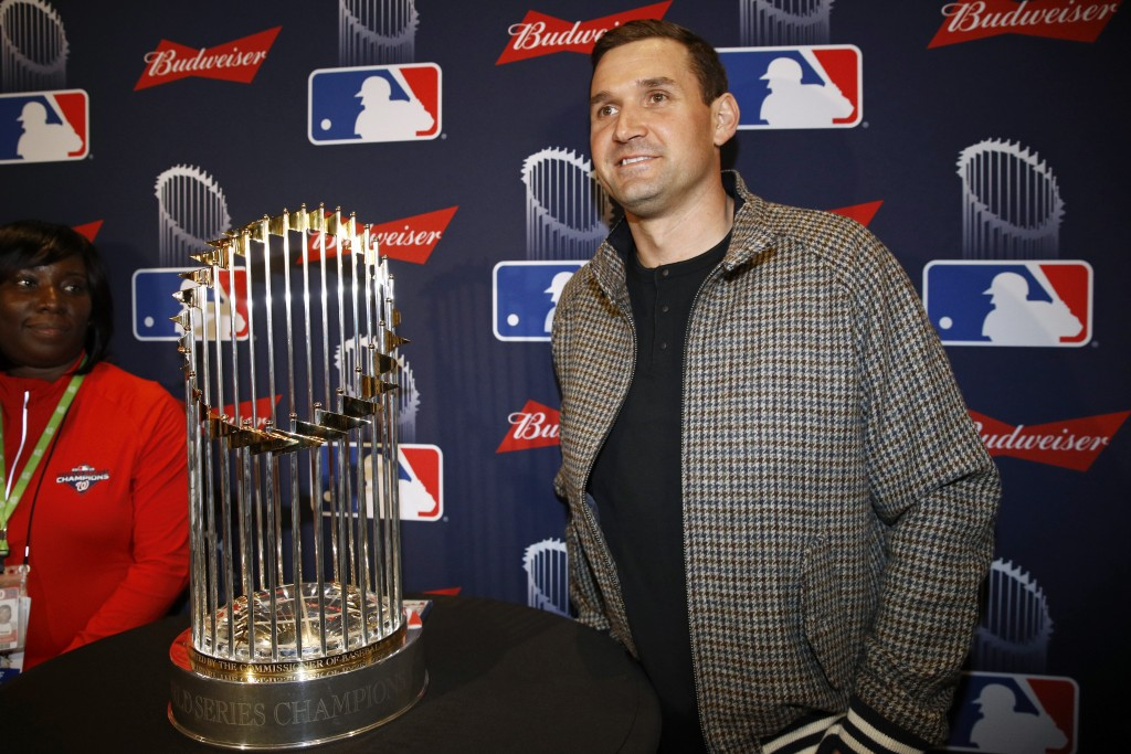 Washington Nationals first baseman Ryan Zimmerman poses with the World Series trophy as he arrives for the premiere of a documentary film on the team'...