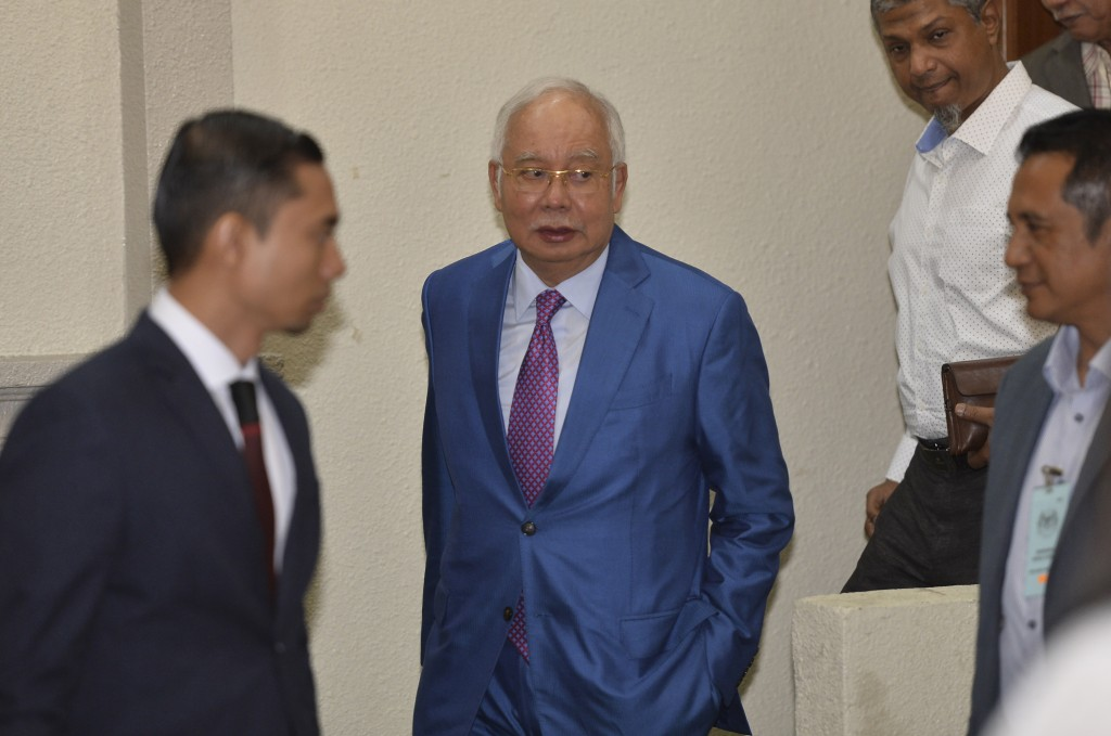 Former Malaysian Prime Minister Najib Razak, center, walks out from the courtroom at the court house in Kuala Lumpur, Malaysia for his corruption tria...