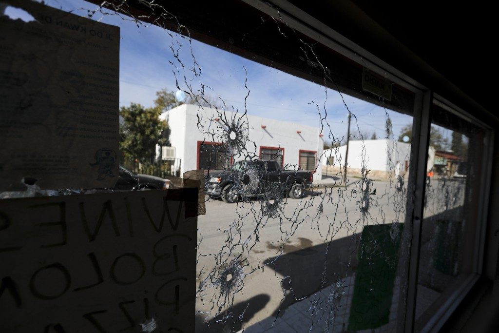A shop's windows are riddled with bullet holes near City Hall after a gunbattle in Villa Union, Mexico, Monday, Dec. 2, 2019. The small town near the ...