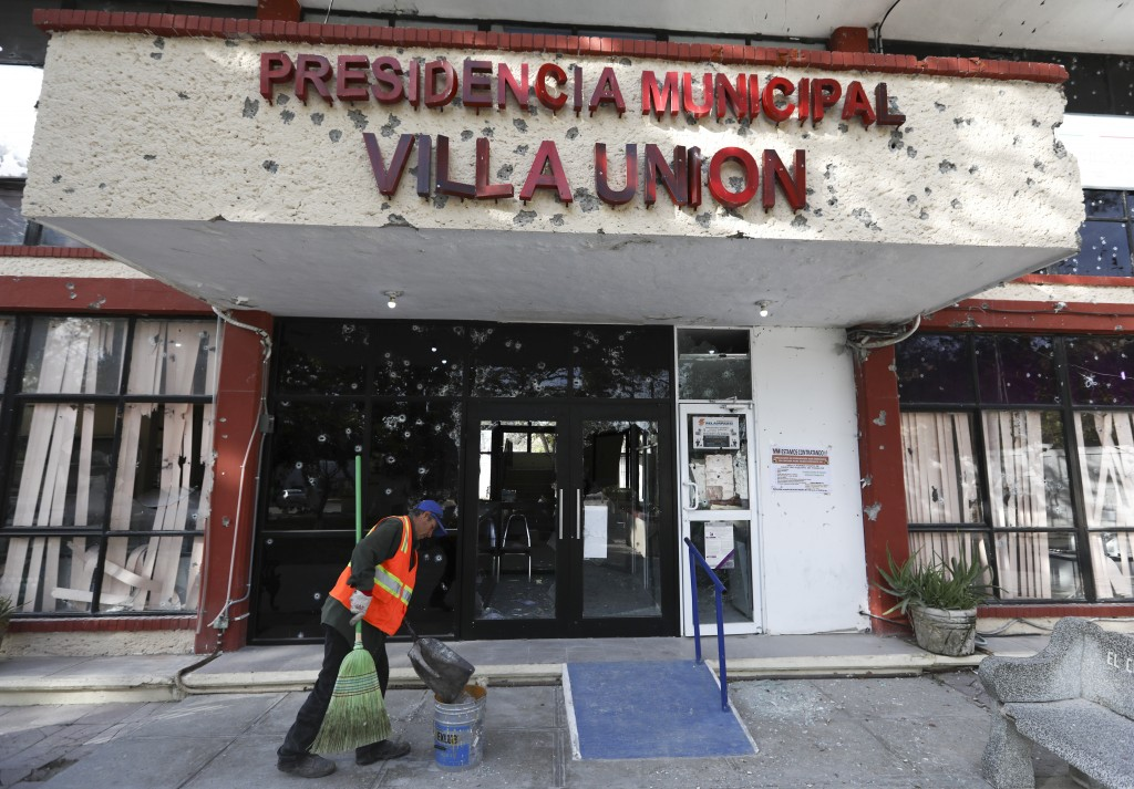 A worker cleans up outside City Hall, riddled with bullet holes, in Villa Union, Mexico, Monday, Dec. 2, 2019. The small town near the U.S.-Mexico bor...