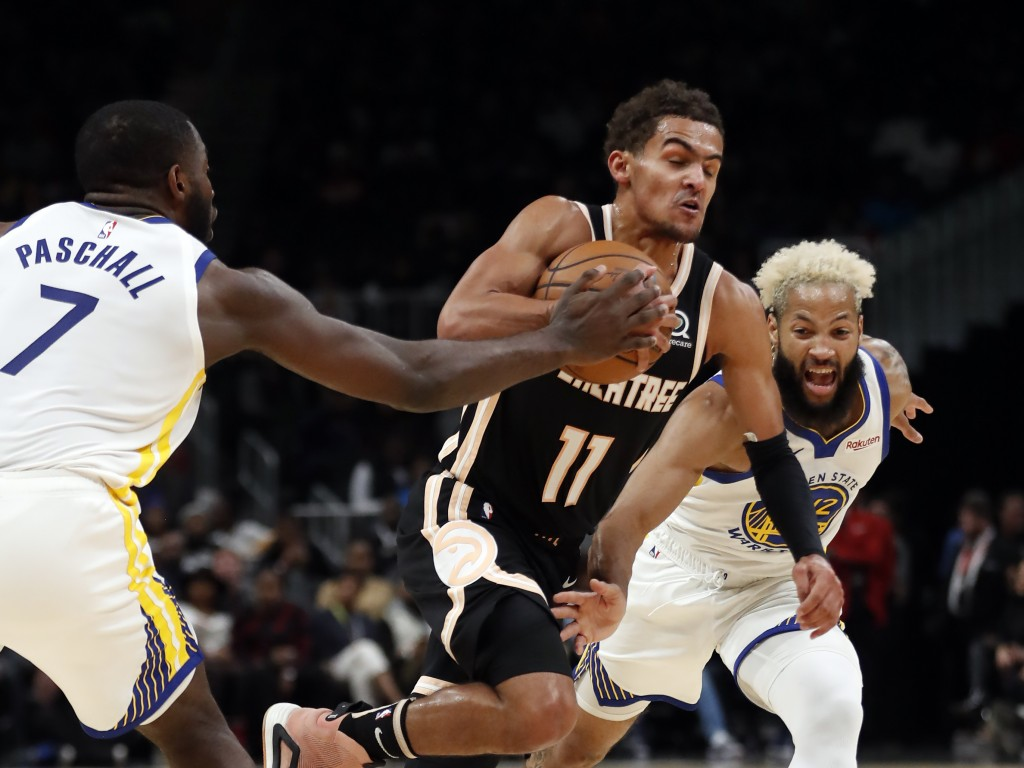 Atlanta Hawks guard Trae Young (11) drives between Golden State Warriors' Eric Paschall (7) and Ky Bowman (12) in the first half of an NBA basketball ...