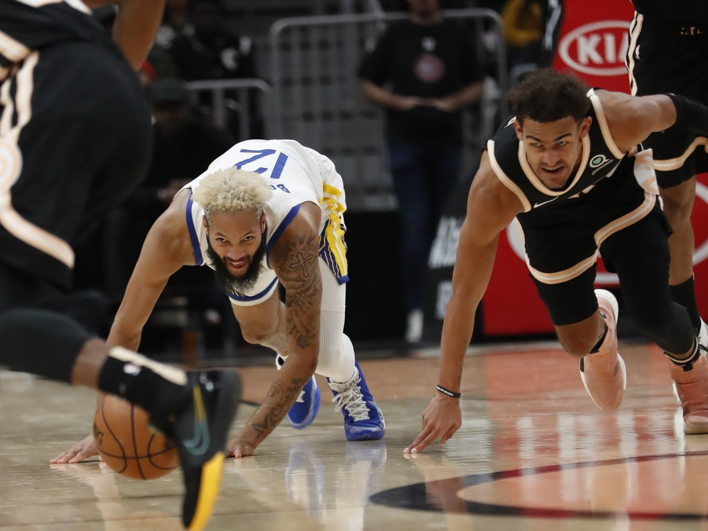 Golden State Warriors guard Ky Bowman (12) and Atlanta Hawks guard Trae Young (11) chase the ball in the first half of an NBA basketball game Monday, ...