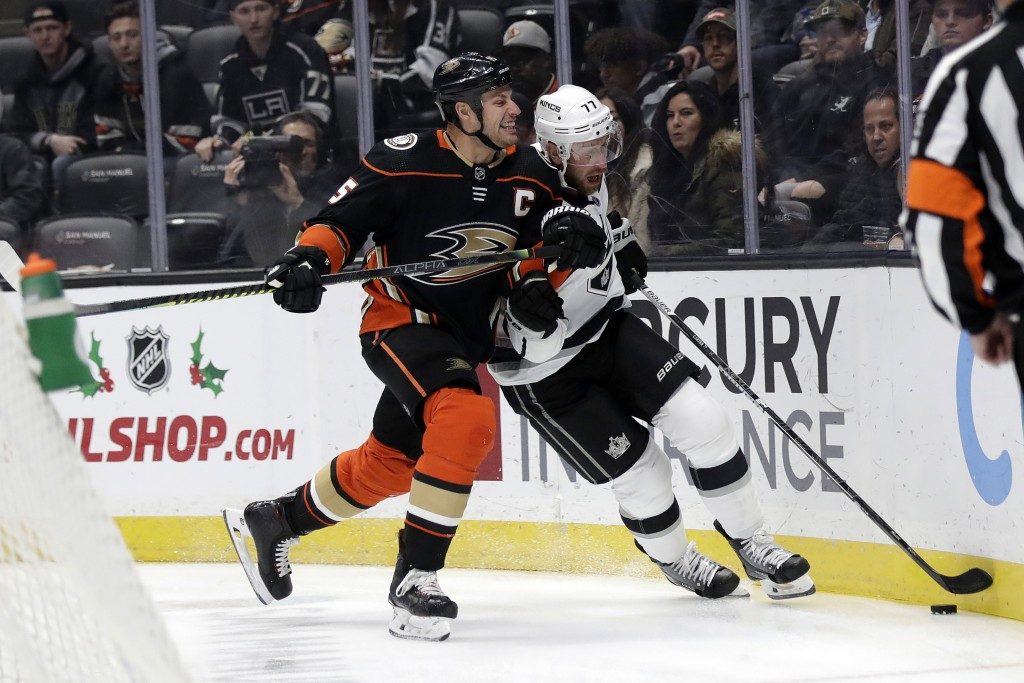 Los Angeles Kings' Jeff Carter, center right, is defended by Anaheim Ducks' Ryan Getzlaf during the first period of an NHL hockey game Monday, Dec. 2,...