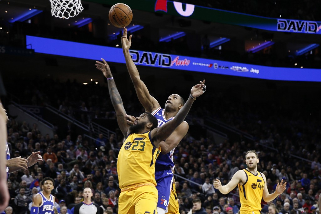 Utah Jazz's Royce O'Neale, center  left, and Philadelphia 76ers' Al Horford leap for a rebound during the first half of an NBA basketball game, Monday...