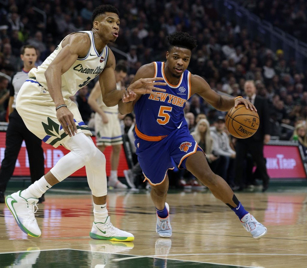 New York Knicks' Dennis Smith Jr. (5) drives against Milwaukee Bucks' Giannis during the first half of an NBA basketball game Monday, Dec. 2, 2019, in...