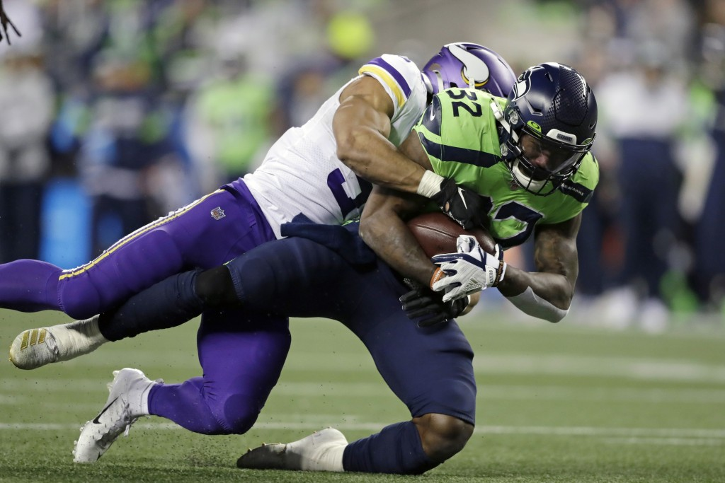 Seattle Seahawks' Chris Carson (32) is brought down by Minnesota Vikings' Eric Wilson on a 26-yard carry during the second half of an NFL football gam...