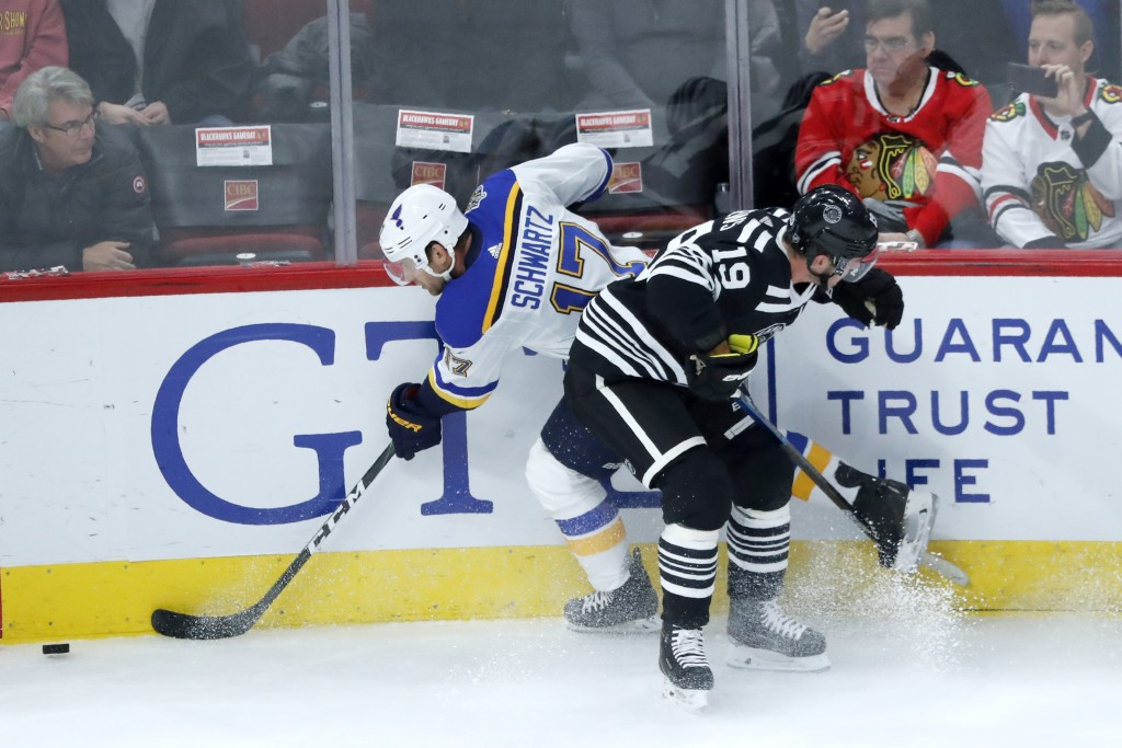Chicago Blackhawks' Jonathan Toews (19) checks St. Louis Blues' Jaden Schwartz against the boards during the first period of an NHL hockey game Monday...