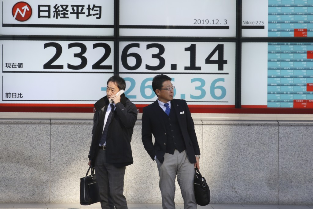 People stand in front of an electronic stock board of a securities firm in Tokyo, Tuesday, Dec. 3, 2019. Asian shares slipped Tuesday, following a dro...