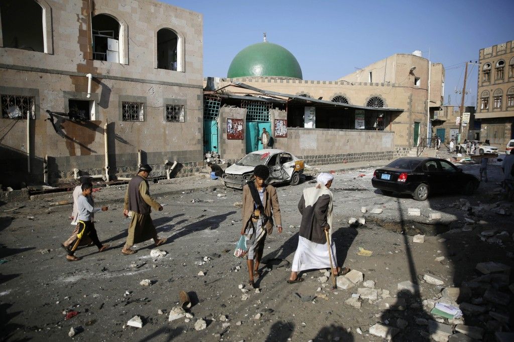 FILE - In this Sept. 3, 2015, file photo people walk at the site of a car bomb attack next to a Shiite mosque in Sanaa, Yemen. Yemen's civil war has e...