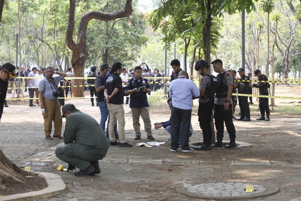 Police investigators inspect the site of an explosion in Jakarta, Indonesia, Tuesday, Dec. 3, 2019. An explosion from a smoke grenade occurred Tuesday...