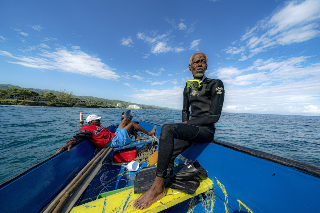 Everton Simpson, right, sits on a boat in-between dives on the White River Fish Sanctuary with Mark Lobban, left, Monday, Feb. 11, 2019, in Ocho Rios,...