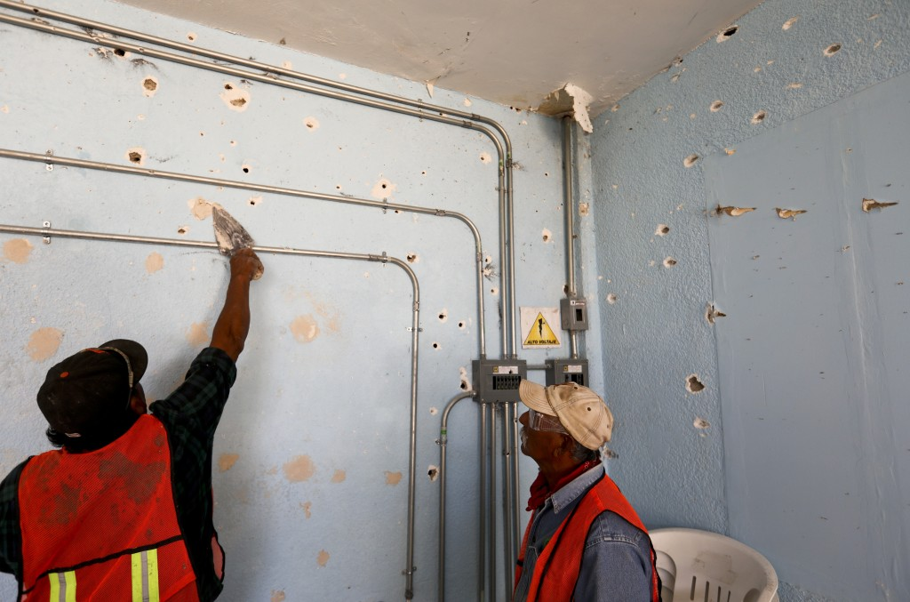 A worker repairs a wall riddled with bullet holes at City Hall in Villa Union, Mexico, Monday, Dec. 2, 2019. The small town near the U.S.-Mexico borde...