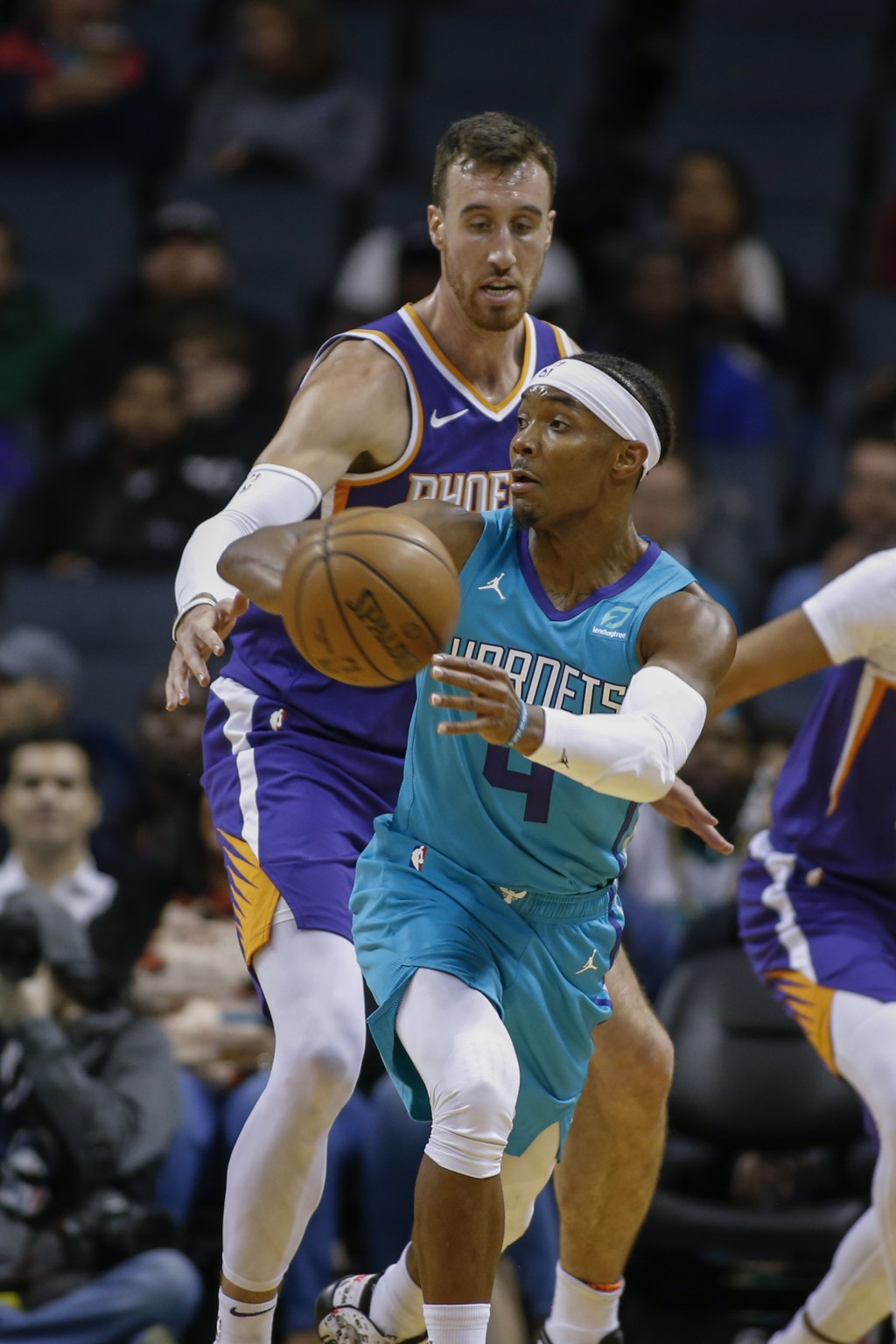 Charlotte Hornets guard Devonte' Graham (4) passes as Phoenix Suns forward Frank Kaminsky, rear, defends in the first half of an NBA basketball game i...
