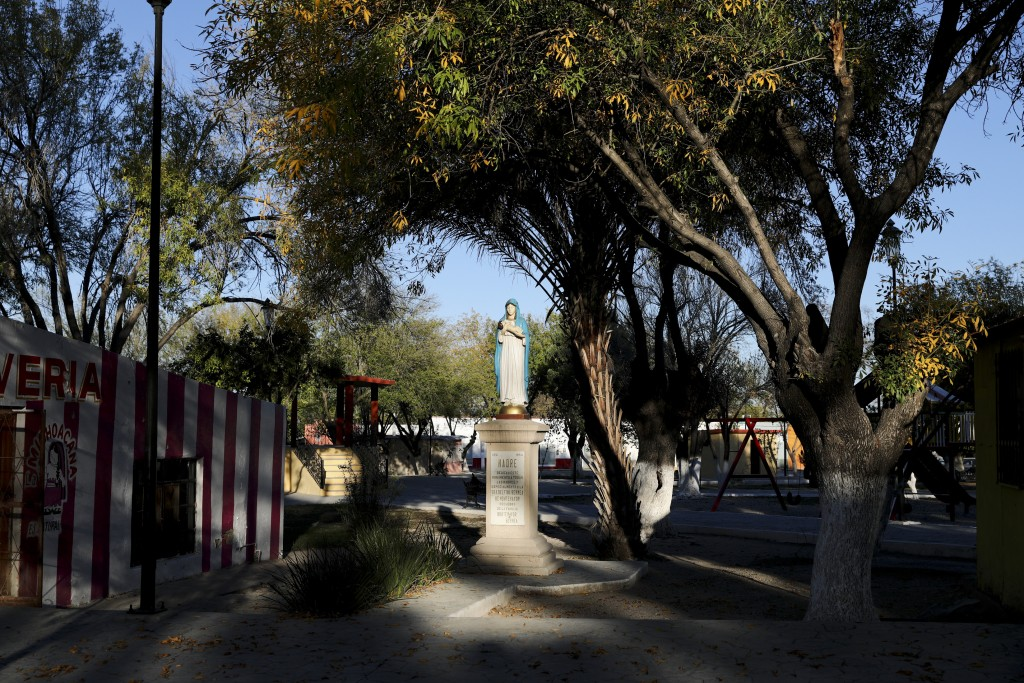 A pocket of light illuminates a statue of the Virgin Mary in Villa Union, Mexico, Monday, Dec. 2, 2019. The small town near the U.S.-Mexico border beg...
