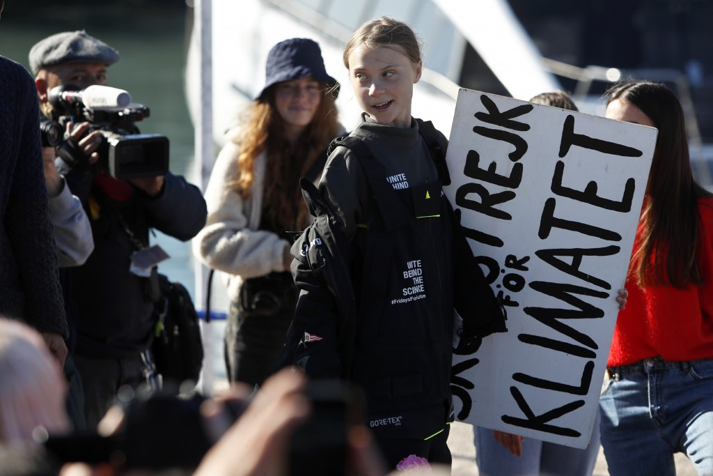 Climate activist Greta Thunberg holds a sign reading 'School strike for the climate' after arriving in Lisbon aboard the sailboat La Vagabonde Tuesday...