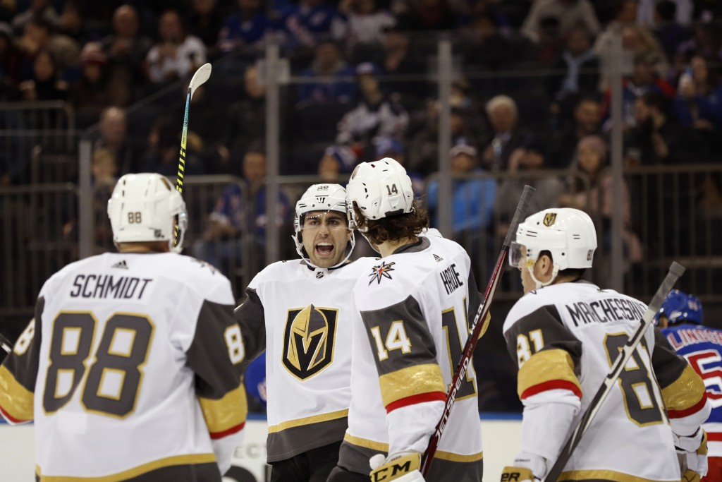 Vegas Golden Knights right wing Alex Tuch, second from left, reacts with teammates after scoring his second goal of an NHL hockey game during the firs...