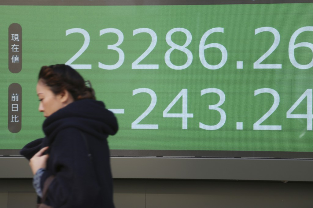A woman walks by an electronic stock board of a securities firm in Tokyo, Tuesday, Dec. 3, 2019. Asian shares slipped Tuesday, following a drop on Wal...