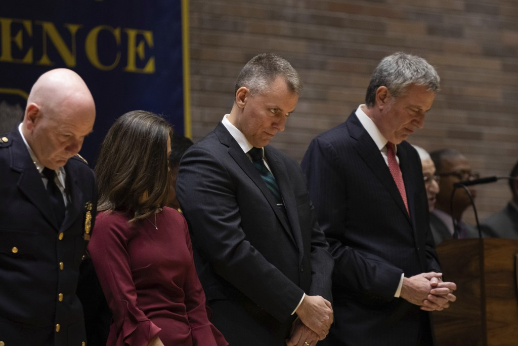 Incoming Police Commissioner Dermot Shea, second from right, bows during the chaplain's convocation at his swearing-in ceremony at police headquarters...