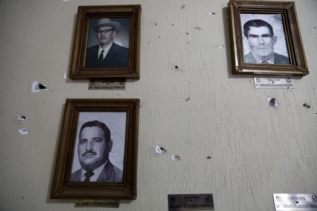 Portraits of former mayors of Villa Union hang on a wall riddled with bullet holes after a gunbattle, inside City Hall, in Villa Union, Mexico, Monday...