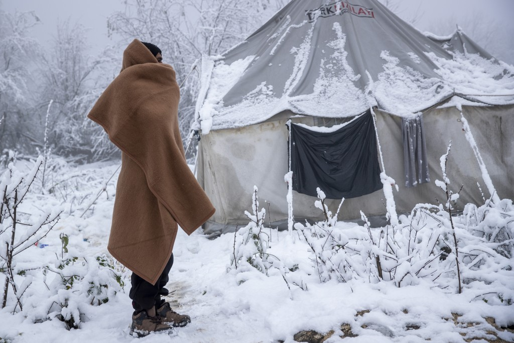 A migrant stands next to a snow covered tent at the Vucjak refugee camp outside Bihac, northwestern Bosnia, Tuesday, Dec. 3, 2019. A European human ri...