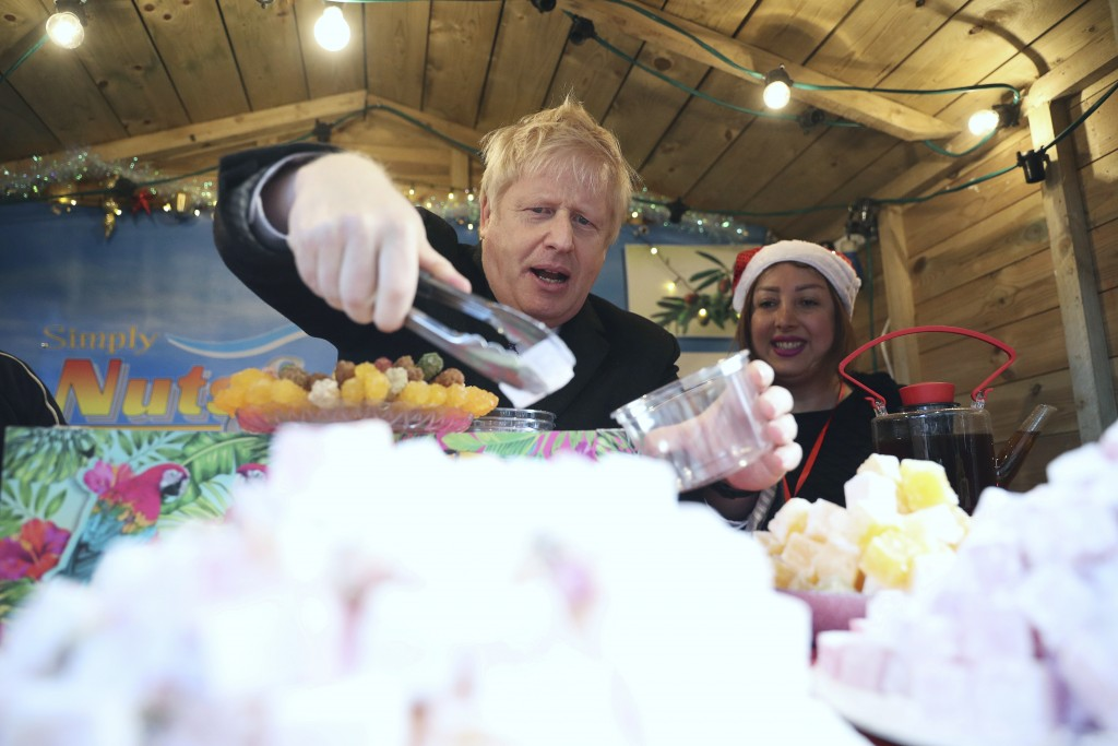 Britain's Prime Minister Boris Johnson, centre, visits a Christmas market whilst on the General Election campaign, in Salisbury, England, Tuesday, Dec...
