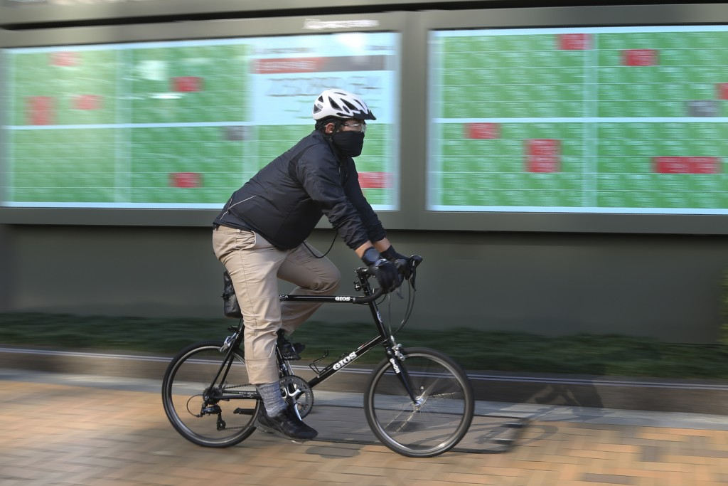 A man cycle pasts by an electronic stock board of a securities firm in Tokyo, Tuesday, Dec. 3, 2019. Asian shares slipped Tuesday, following a drop on...