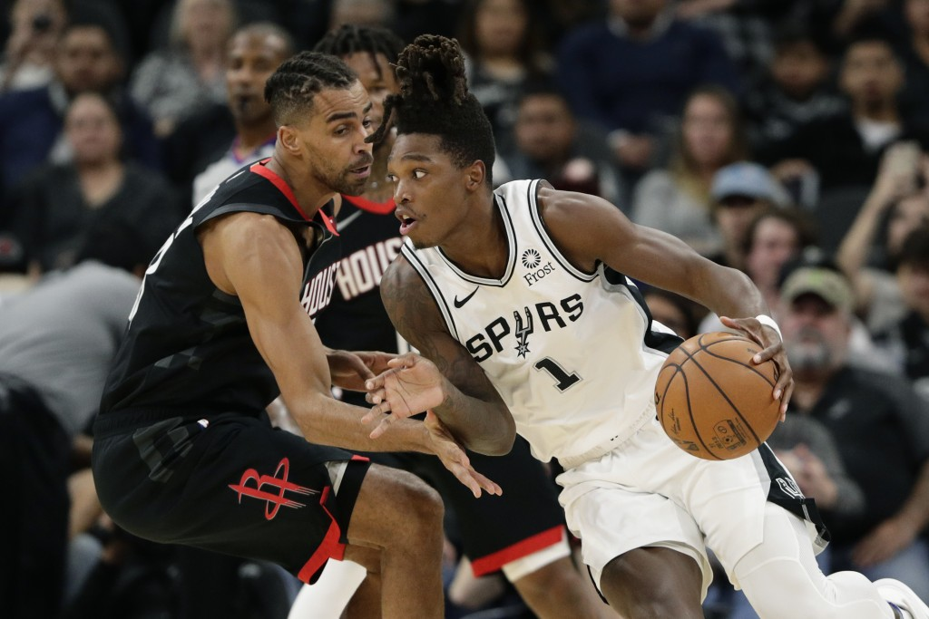 San Antonio Spurs guard Lonnie Walker IV (1) drives around Houston Rockets forward Thabo Sefolosha during the first half of an NBA basketball game in ...