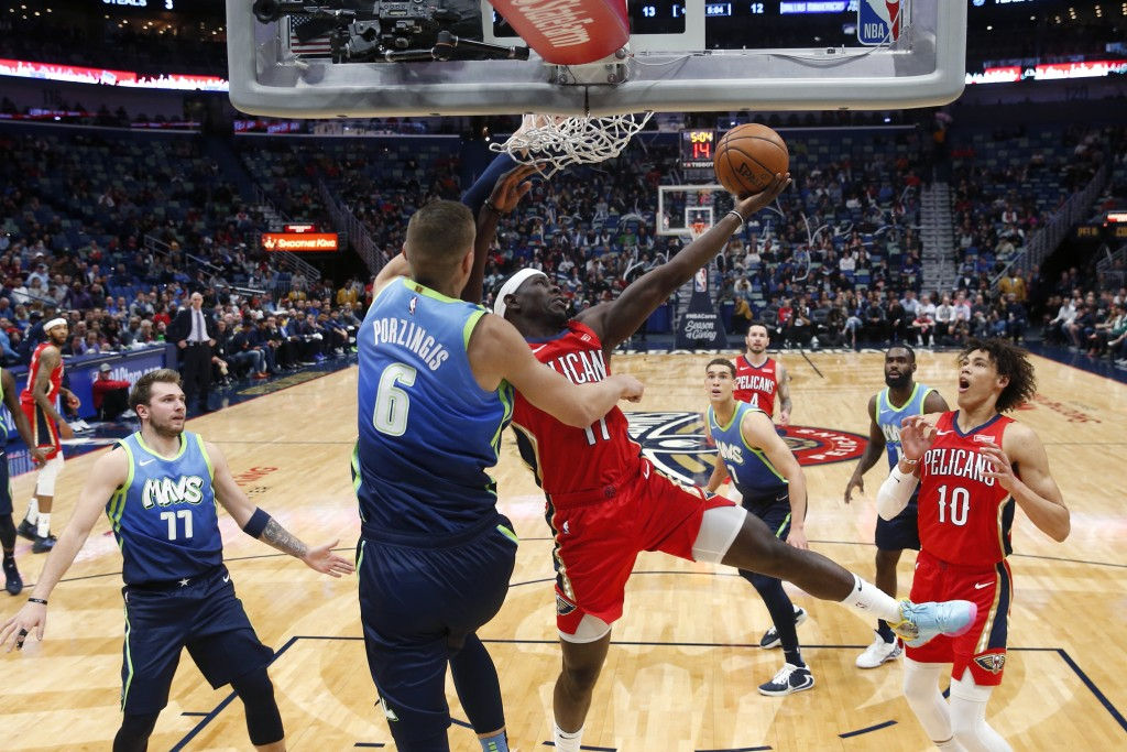 New Orleans Pelicans guard Jrue Holiday (11) goes to the basket against Dallas Mavericks forward Kristaps Porzingis (6) in the first half of an NBA ba...