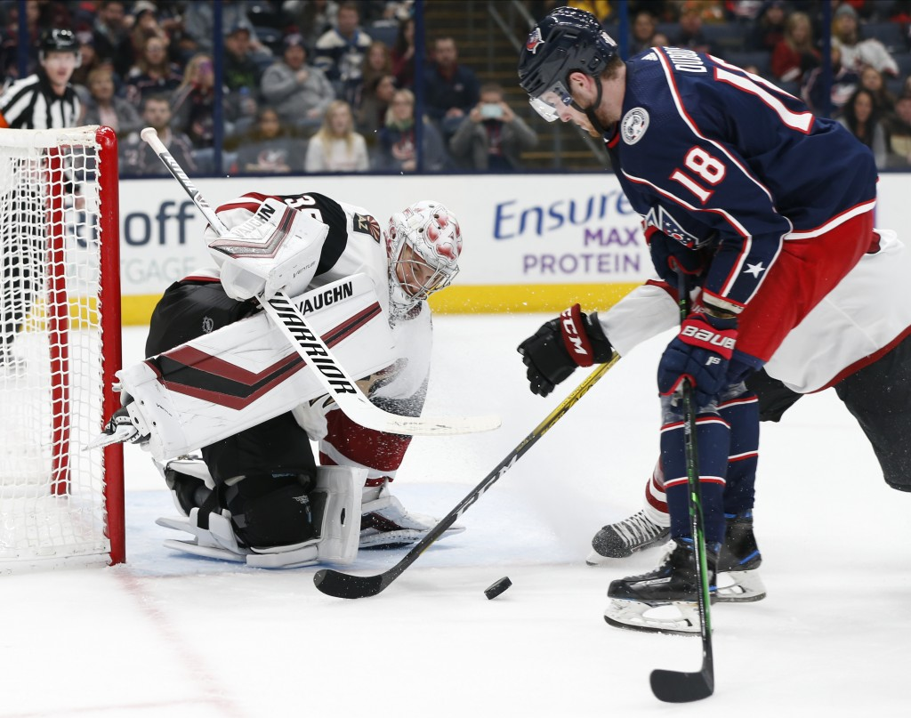 Arizona Coyotes' Darcy Kuemper, left, makes a save against Columbus Blue Jackets' Pierre-Luc Dubois during the second period of an NHL hockey game Tue...