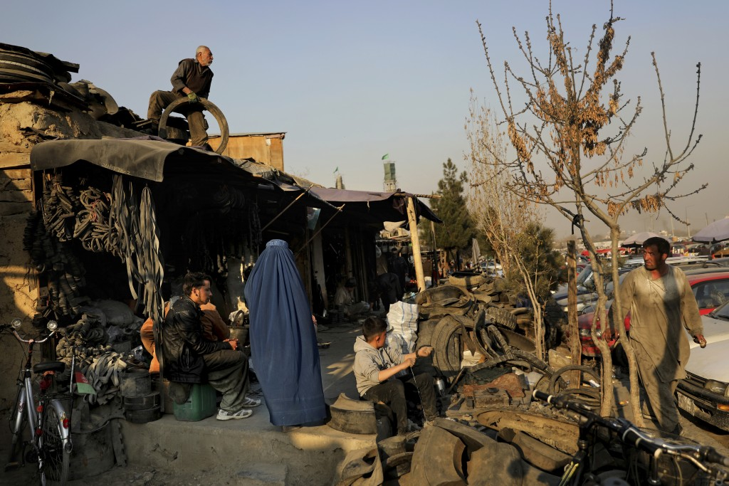 An Afghan man prepares to throw a used tire from the roof of his shop as a burqa clad woman walks past at a market place in Kabul, Afghanistan, Wednes...