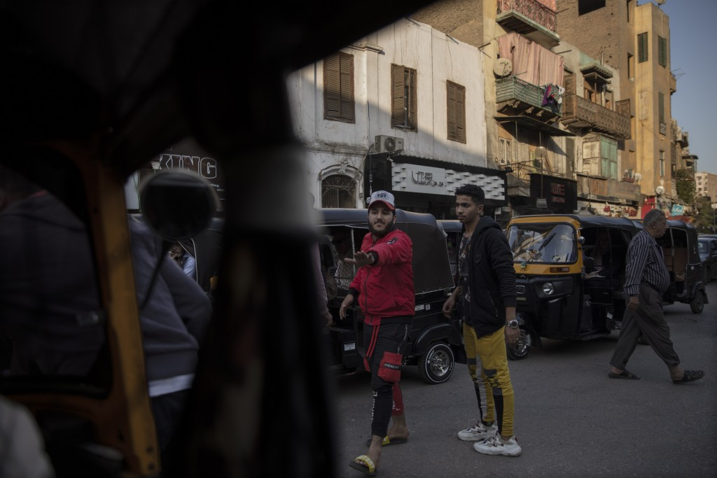 In this Nov. 19, 2019 photo, citizens help tuk-tuk drivers maneuver in traffic at a slum area in Cairo, Egypt. Motorized rickshaws known as tuk-tuks h...