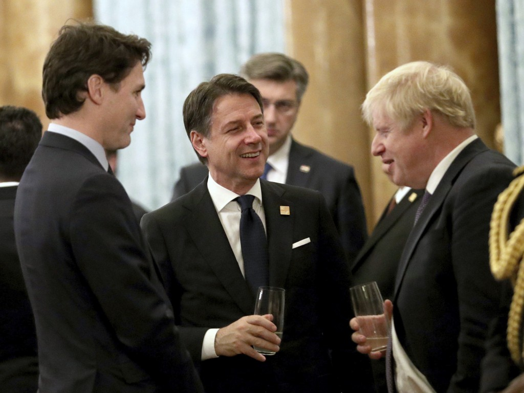 Britain's Prime Minister Boris Johnson talks to Canadian Prime Minister Justin Trudeau, left, and Italian Prime Minister Giuseppe Conte during a recep...