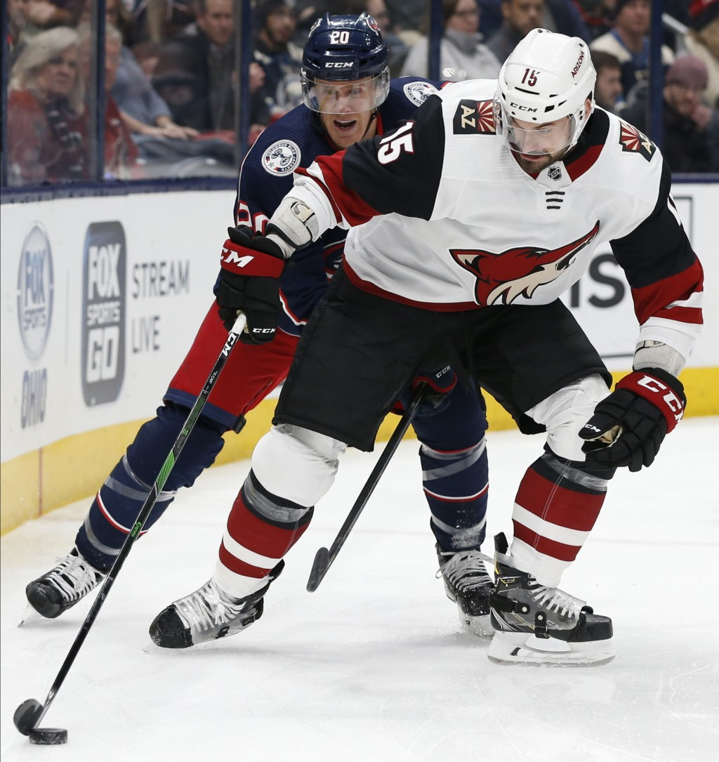 Columbus Blue Jackets' Riley Nash, left, tries to steal the puck from Arizona Coyotes' Brad Richardson during the first period of an NHL hockey game T...