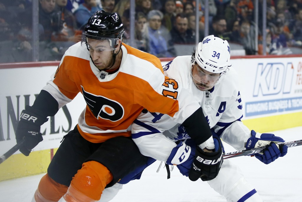 Philadelphia Flyers' Kevin Hayes (13) and Toronto Maple Leafs' Auston Matthews (34) battle for position during the third period of an NHL hockey game,...