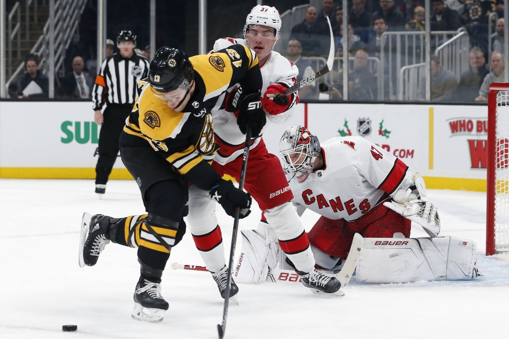 Boston Bruins' Charlie Coyle (13) tries to control the puck in front of Carolina Hurricanes' Andrei Svechnikov (37) and James Reimer (47) during the s...