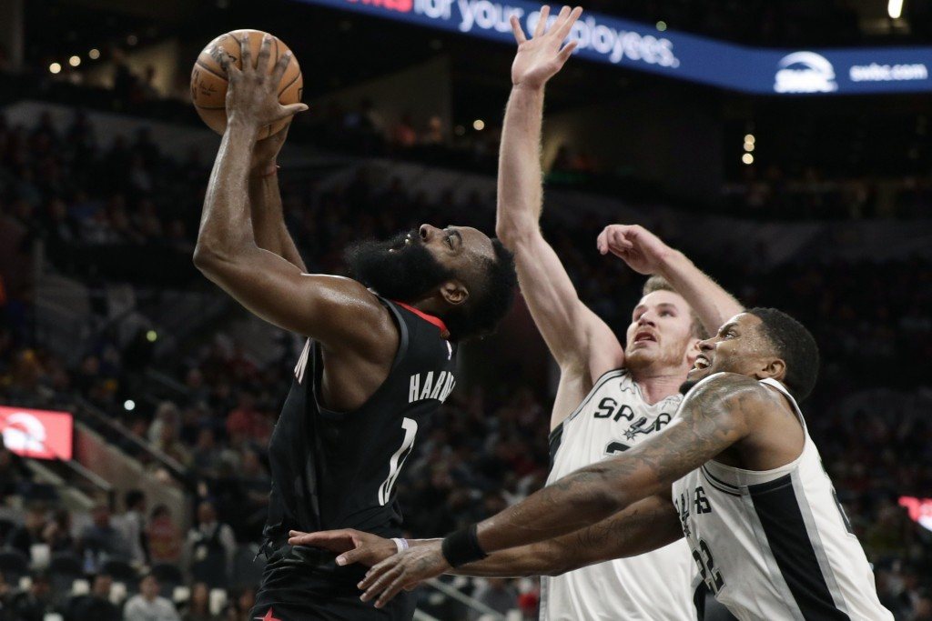Houston Rockets guard James Harden (13) drives past San Antonio Spurs forward Rudy Gay, right, and center Jakob Poeltl during the first half of an NBA...