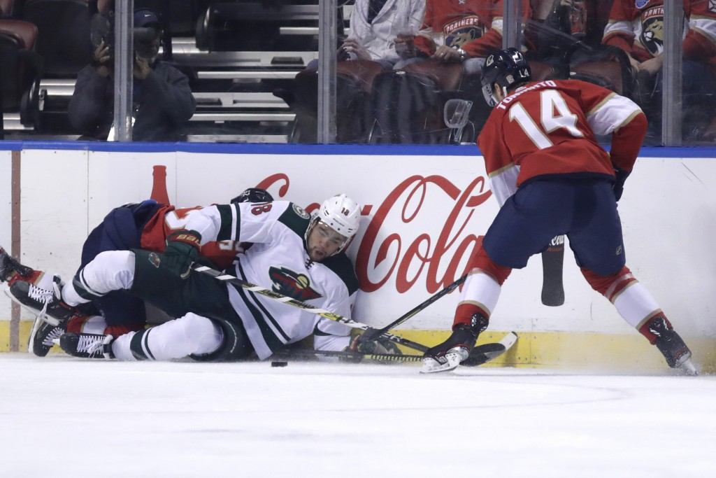 Minnesota Wild left wing Jordan Greenway (18) and Florida Panthers center Dominic Toninato (14) go for the puck during the first period of an NHL hock...