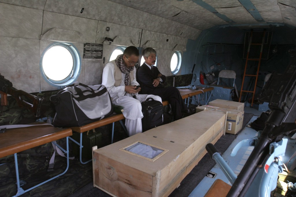 File-In this Thursday, Aug. 28, 2008, photo, Japanese doctor Tetsu Nakamura, center right, sits with unidentified man, near the casket of Japanese aid...