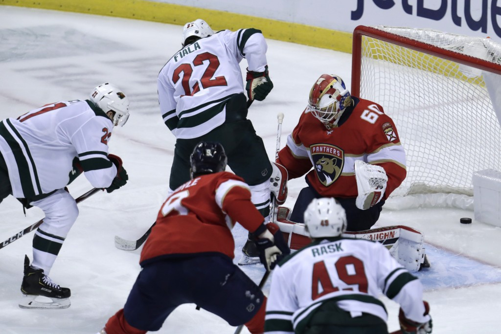 Minnesota Wild defenseman Carson Soucy, left, scores a goal against goaltender Chris Driedger (60) during the third period of an NHL hockey game, Tues...